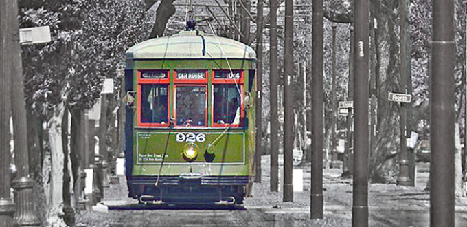 green streetcar moves along the tracks, background is black and white